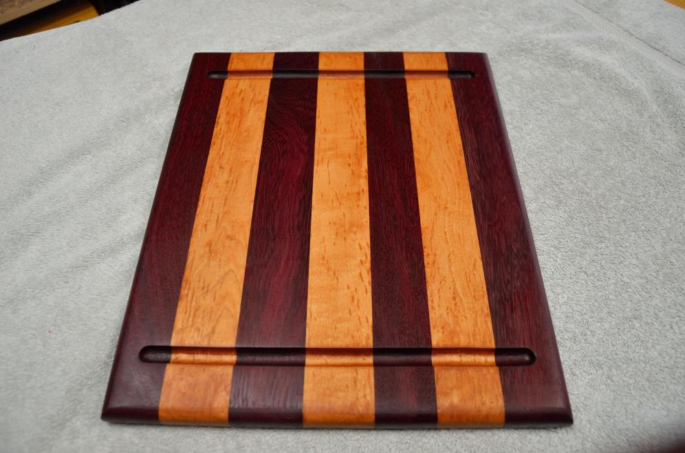 Commissioned restoration project. This 20-year old board was presented to me in two pieces: a glue joint had failed. The pieces were squared up, re-glued, sanded and re-finished. Purpleheart and maple.