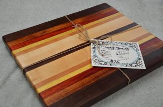 """A board for the world traveler, with woods from 4 continents. 12"""" x 16"""" x 1-1/8"""". Black walnut (North America), Jatoba (South America), Padauk (Africa), Yellowheart (South America), Cherry (North America), Hard Maple (North America) and Jarrah (Australia) edge grain."""