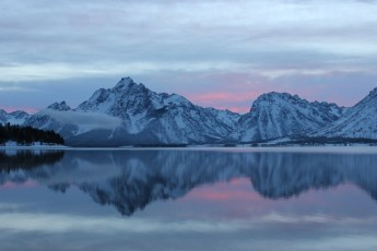 """A stunning sunset over Grand Teton National Park in Wyoming. Christina Adele Warburg took this photo of Mount Moran and Jackson Lake from the park's Colter Bay District a few weeks ago after a recent snow. """"I had to snowshoe to the edge of the lake for the sunset. The effort was definitely worth the reward,"""" says Christina. Posted on Tumblr by the US Department of the Interior, 12/1/14."""