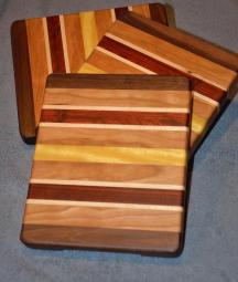 "Cheese Board # 15 - 011. Black Walnut, Cherry, Hard Maple, Padauk and Yellowheart. 8"" x 9"" x 1""."
