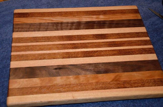 "Cutting Board # 15 - 026. Honey Locust, Jatoba, Cherry and Curly Black Walnut. 13"" x 16"" x 1-1/4""."