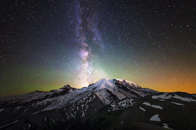 The Milky Way appears over the summit of Mount Rainier in Washington's Mount Rainier National Park. The streaks of light on the Mount Rainier: those are climbers getting an alpine start and heading towards the summit. Photo by Stephen Byrne. Posted on Tumblr by the US Department of the Interior, 6/27/15.