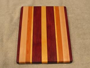 "Cheese Board # 15 - 064. Purpleheart, Hard Maple, Cherry & Yellowheart. 9"" x 11"" x 3/4""."