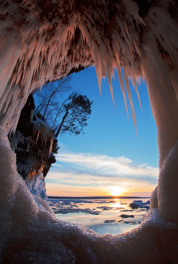 "Over thousands of years, Lake Superior carved out caves in the sandstone cliffs of the Wisconsin lakeshore. Today, when conditions are right, you can hike out across the solid water (ice) and see these remarkable formations clad in snow and ice at Apostle Islands National Lakeshore. Photo of ""The Keyhole"" by Michael DeWitt. Posted on Tumblr by the US Department of the Interior, 12/29/15."