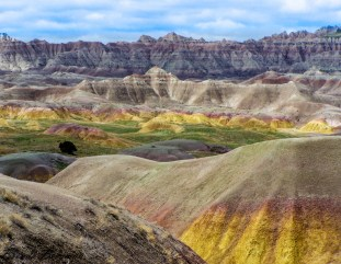 Cotton-candy yellows and pinks color the hills of Badlands National Park in South Dakota. The Badlands' striking formations contain one of the world's richest fossil beds, carrying clues to ancient mammals like rhinos and saber-toothed cats that once roamed here. Photo by Brenda Bergman. Posted on Tumblr by the US Department of the Interior, 2/17/16.