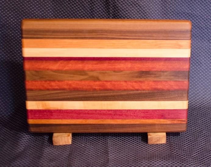 "Cheese Board 16 - 010. Edge Grain. Black Walnut, Cherry, Hard Maple, Purpleheart & Jarrah. 9"" x 13"" x 1""."