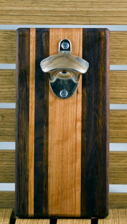 "Magic Bottle Opener 16 - 015. Wall mount. Black Walnut, Cherry & Jatoba. Approximately 5"" x 10"" x 3/4""."