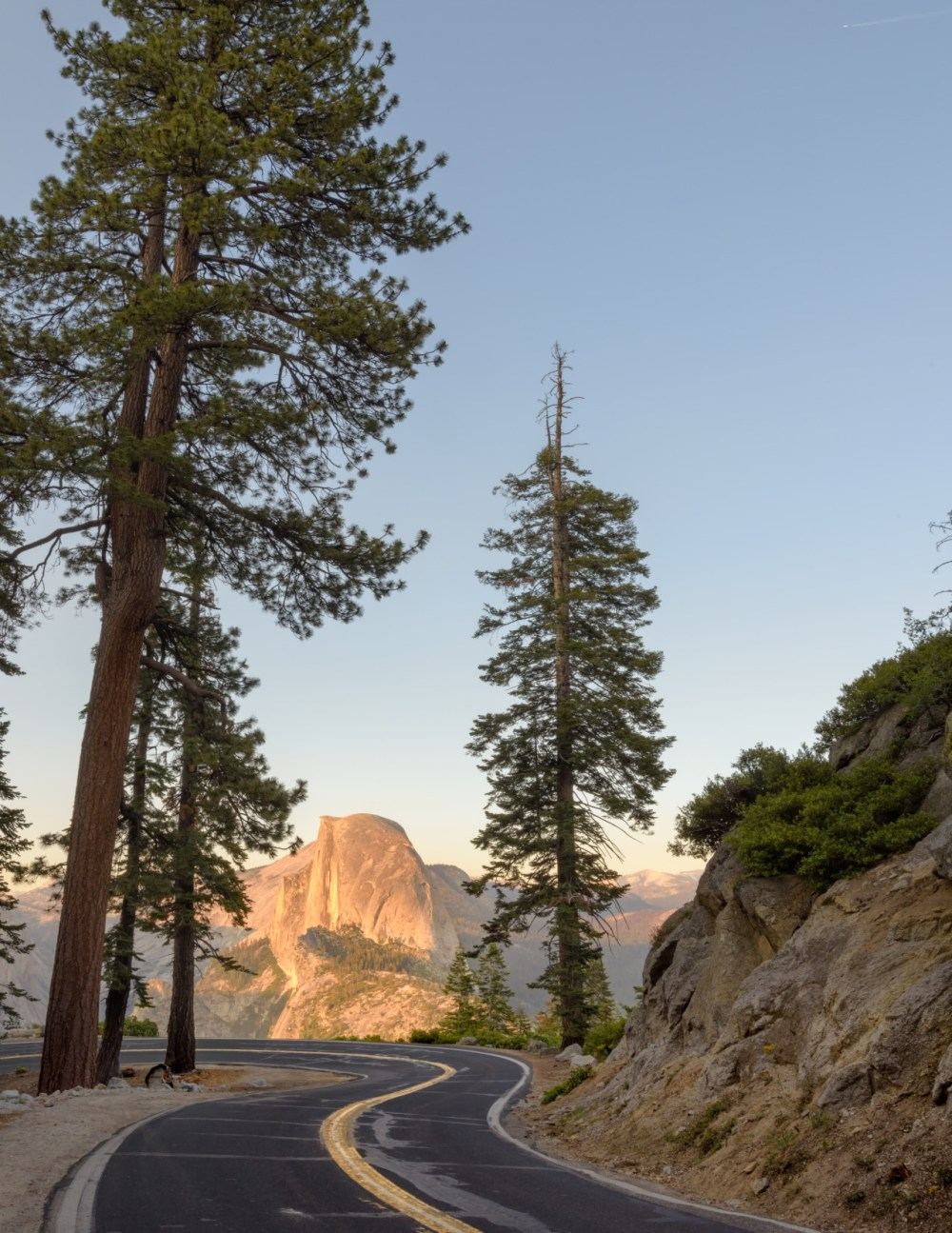 """""""There's just something about a winding road that ignites wanderlust,"""" says photographer Kathryn Dyer! At an impromptu stop in California's Yosemite National Park, Kathryn captured this incredible shot of Half Dome shining golden from a beautiful alpenglow and framed by trees. When you visit public lands, you never know what amazing vistas you'll find! Photo by Kathryn Dyer. Posted on Tumblr by the US Department of the Interior, 9/25/16."""