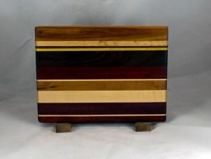 "Cheese Board 16 - 056. Chaos Board. Canarywood, Padauk, Hard Maple, Yellowheart, Black Walnut, Goncalo Alves & Bloodwood. 9"" x 12"" x 5/8""."