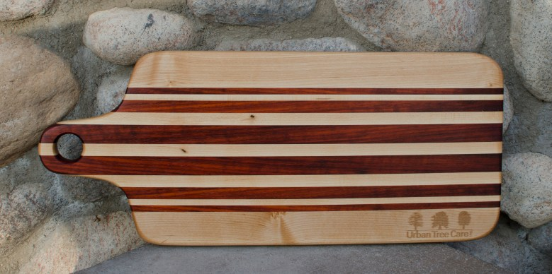 "Engraved 16 - 56. Bread board made for Urban Tree Care. Hard Maple and Bloodwood. 8"" x 20"" x 1""."
