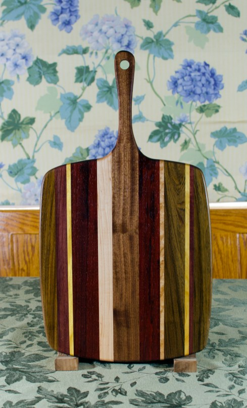 """Sous Chef 17 - 912. Black Walnut, Purpleheart, Yellowheart, Bubinga, Hard Maple & Sapele. Chaos Board. Large size, with the work space approximately 11"""" x 15"""", with the handle extending for an additional 6""""."""