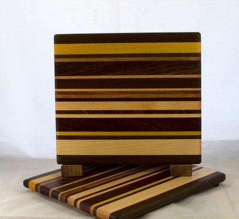 "Cheese Board 17 - 334. Chaos Board. Padauk, Black Walnut, Yellowheart, Hard Maple, Canarywood, Honey Locust, Bubinga & Bloodwood. 8"" x 11"" x 5/8""."