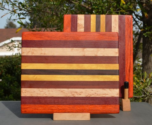 "Cheese Board 18- 108. Padauk, Purpleheart, Birds Eye Maple, Bloodwood, Yellowheart & Jarrah. 9"" x 11"" x 5/8""."