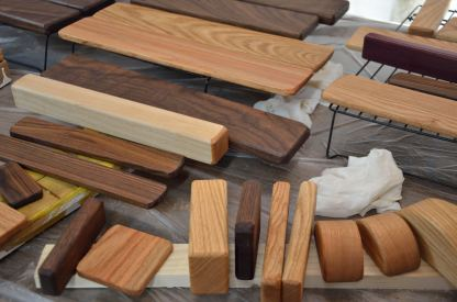 Walnut is the dark brown, red oak is the light brown wood, and hard maple is the long white piece in the center of the photo.