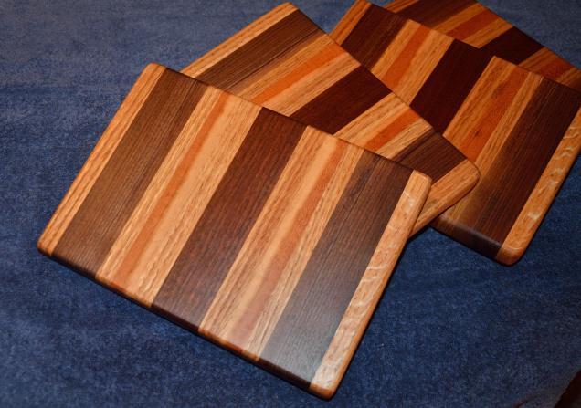 "# 15 Cheese Board, $30. Edge grain. Oak, walnut, and cherry. 8"" x 10"" x 1""."