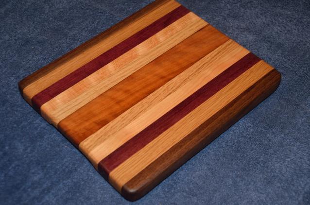 "Cheese board # 15 - 001. Black Walnut, Hard Maple, Red Oak, Purpleheart and Cherry. 9"" x 12"" x 1""."