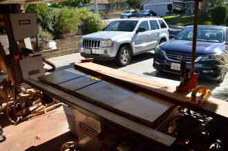 This is the table saw set up for cove cuts, the sweeping curves under each edge of the large surfboards. The board placed across the saw becomes the fence that the boards are pushed into as they go through the blade.