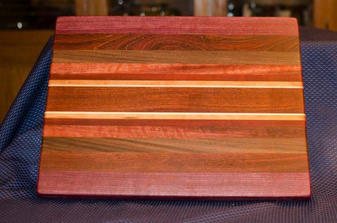"Cutting Board 16 - Edge 007. Purpleheart, Jatoba, Black Walnut, Bloodwood, Cherry & Hard Maple. Edge Grain. 12"" x 16"" x 1-1/4""."