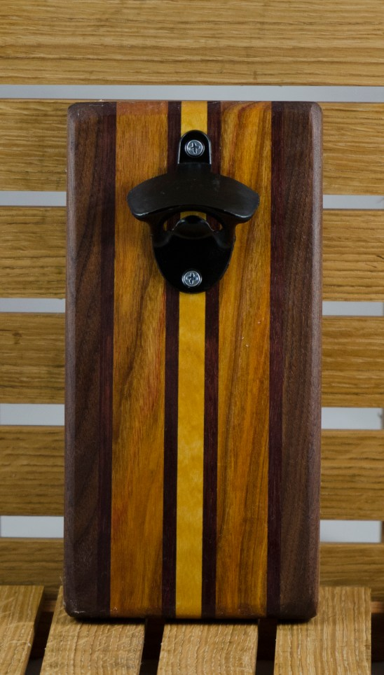 "Magic Bottle Opener 16 - 081. Wall mount. Black Walnut, Canarywood & Yellowheart. Approximately 5"" x 10"" x 3/4""."
