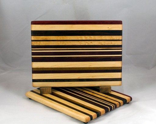 "Cheese Board 16 - 068. Chaos Board. Padauk, Hard Maple, Black Walnut, Jatoba, Purpleheart, Goncalo Alves & Bloodwood. 8"" x 11"" x 3/4""."