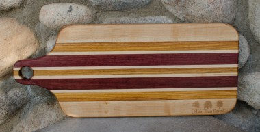 """Engraved 16 - 52. Bread board made for Urban Tree Care. Hard Maple, Canarywood & Purpleheart. 8"""" x 20"""" x 1""""."""