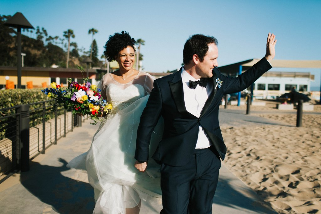 Bride & Groom walk on beach and wave, Santa Monica, CA
