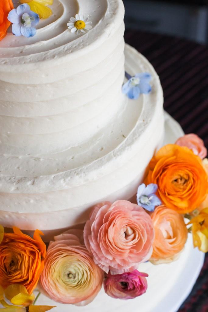 Three-tiered white textured wedding cake with peach, orange, pink and blue florals