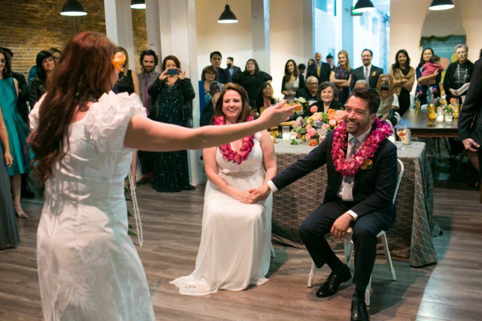 bride & groom enjoy a hula dancer at their wedding reception