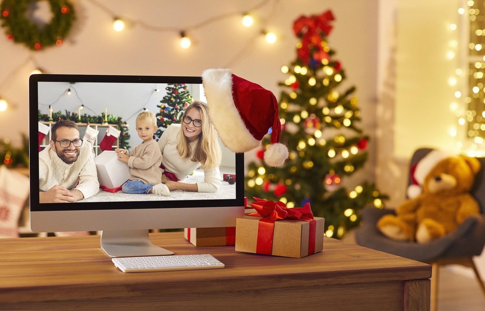 Holiday scene with a family on a computer. There is also a christmas tree, a santa hat hanging off the screen, and a nearby present resting on the desk. Moxie Family Therapy offers emdr therapy, counseling for women in orange county, family therapy, and more. Contact us today for the support you deserve!
