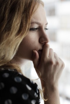 Sad woman with hand to her mouth looking through a window. She is wondering if emdr therapy could help her overcome past trauma. Moxie Family Therapy offers emdr therapy in Orange County, California. Contact our emdr trained therapist for emdr treatment for ptsd, emdr trauma therapy, and more.