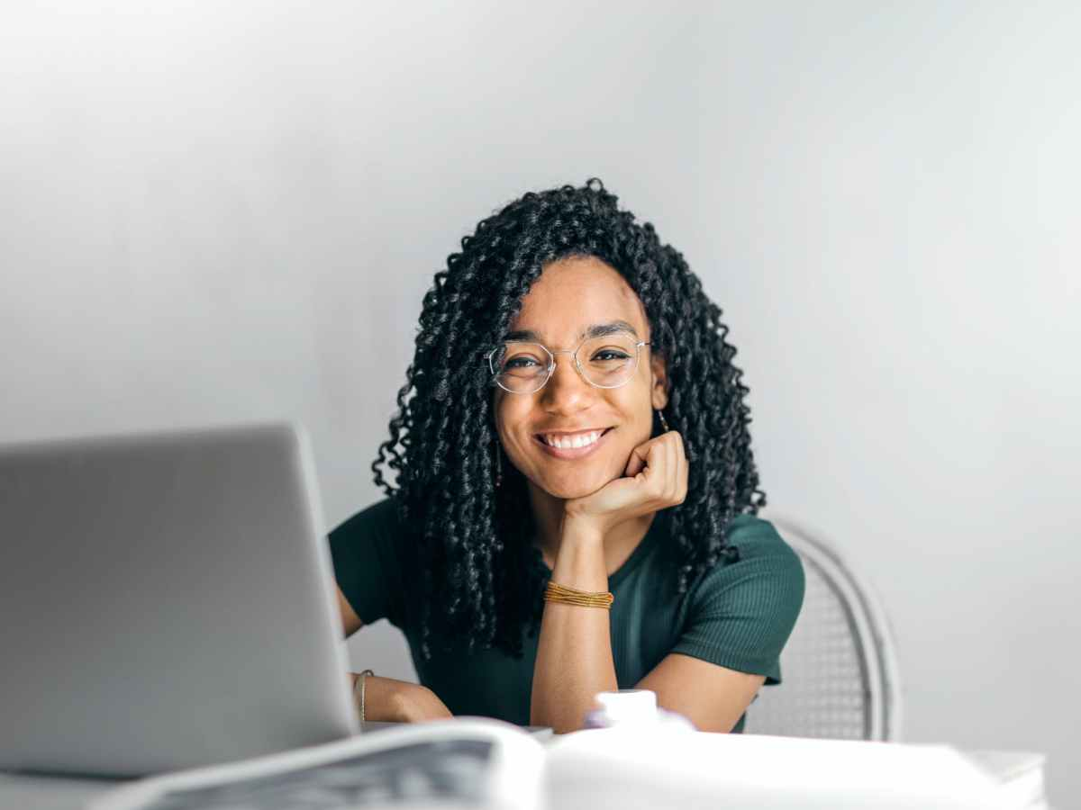 happy african american woman sitting at table with laptop participating in an online therapy session