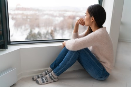 Depressed young girl looks out the window in winter. She is sitting on the ground next to the window, thinking about if EMDR therapy could give her the support she needs. Moxie Family Therapy offers emdr therapy in orange county. Contact our emdr trained therapist for emdr treatment for ptsd, emdr therapy for trauma, and other services.