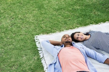 A smiling couple lay on a blanket in the lush grass. Their relationship has never felt stronger after seeing a marriage counselor in Orange County, CA. Moxie Family Therapy offers online marriage counseling, couples therapy in Orange County, CA, and more. Contact us today to start couples therapy and marriage counseling.