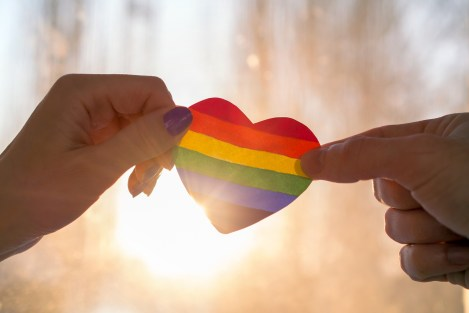 Two hands hold either side of a heart painted like a LGBTQ flag, silhouetted against sun. This symbolizes the love felt by members of the lgbtq community. We offer lgbt therapy in Santa Ana, online lgbtq therapy in California, and more. Contact an lgbtq therapist for support today!