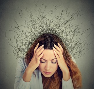 A woman holds both sides of her head with a pained expression on her face. Her hair frizzes in all directions, creating question marks and exclamation points. This could represent the mental fog that comes with anxiety. Moxie Family Therapy offers anxiety treatment in Orange County, CA. Contact an anxiety therapist for more info on EMDR therapy for anxiety and other services.