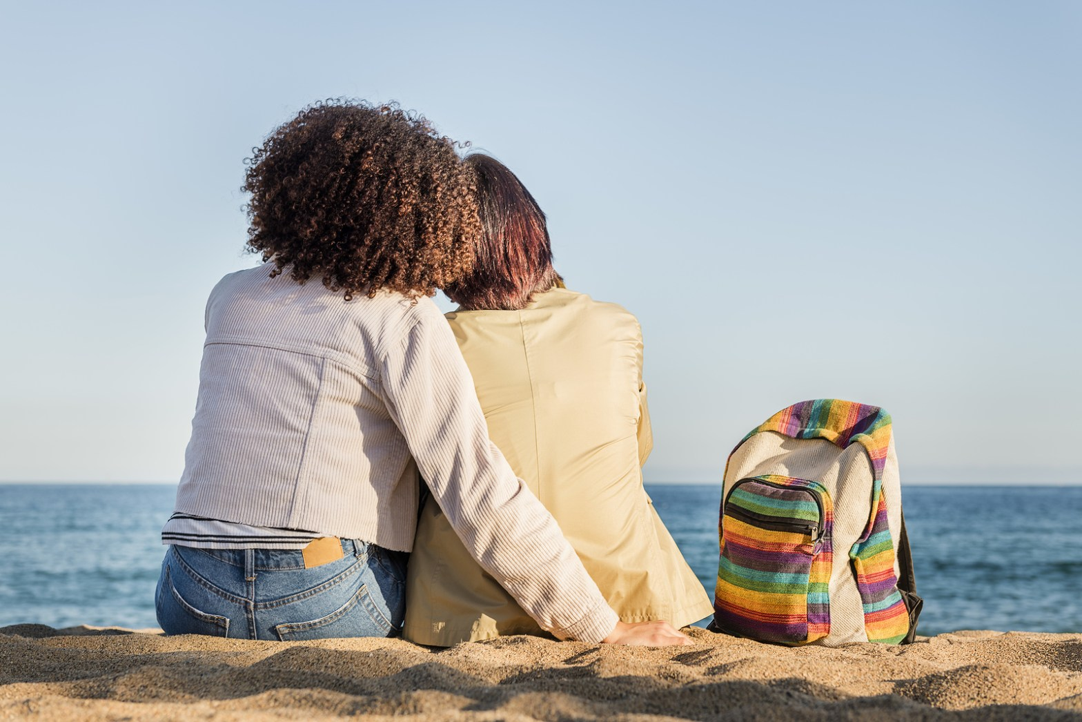 A lesbian couple embrace in front of the sea next to a backpack with the rainbow flag colors as the sun sets behind them. This could symbolize the love forged after meeting with an LGBT therapist to talk through their issues. We offer counseling for women in Orange County, CA, online LGBTQ therapy, and other services.