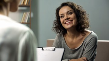 A woman smiles brightly as a person with a clipboard sits across from them. This could represent trauma therapy in Orange County, CA. Contact a trauma therapist for support with online therapy for trauma, EMDR therapy and more.