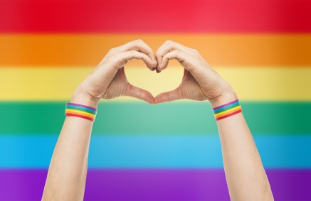 A pair of hands make a heart gesture in front of a pride flag. LGBTQ therapy in Orange County, CA can offer support for LGBTQIA+ issues. Contact a LGBTQ therapist for more information today!