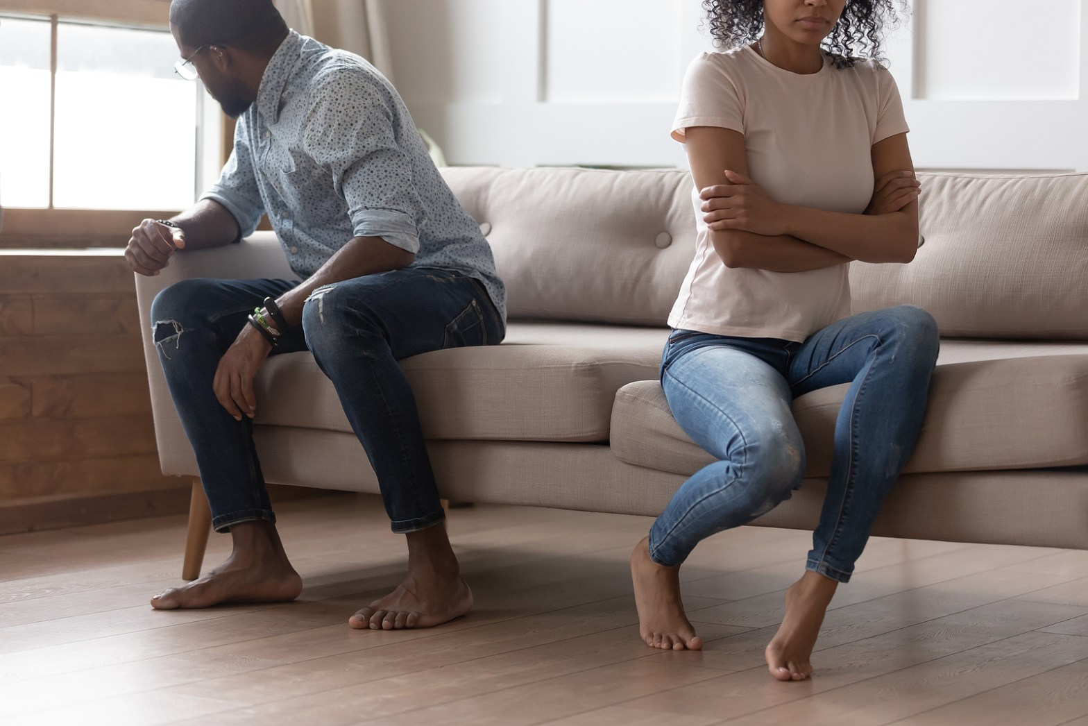 Spouses Sitting On Couch Separate From Each Other After an argument. Trauma therapy in Orange County, CA can you cope with a major breakup. Learn more about counseling for women from a trauma therapist today!