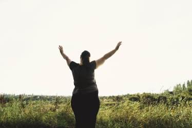 A woman stands in a field with her arms extended in celebration. This could represent being at peace with one's self. Contact a therapist for loneliness in Orange County, CA to learn more about combating loneliness with therapy for loneliness in Orange County, CA today! 92701 | 92805 | 92806