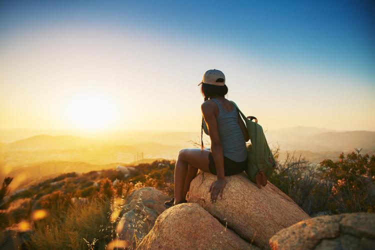 A woman sits on a rock as she watches the sunrise over the mountains. This could represent combating loneliness in Orange County, CA. A relationship therapist can offer support with therapy for loneliness in Orange County, CA and other services. 92704 | 92683 | 92804