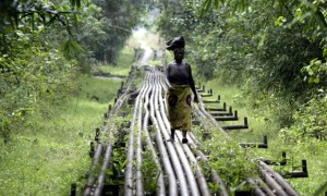 A woman walks along an oil pipeline in Warri, Nigeria