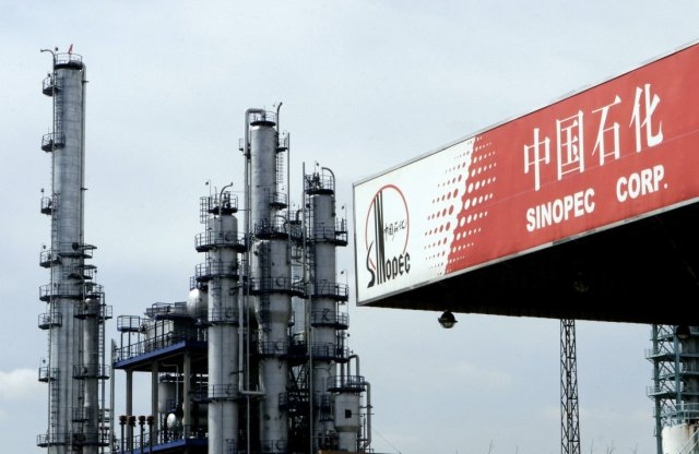 A Sinopec gas station stands in front of a Sinopec oil refin