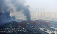 Smoke rises from shipping containers after explosions at Binhai new district in Tianjin