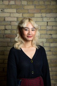 Photo of Khin standing in front of a brick wall