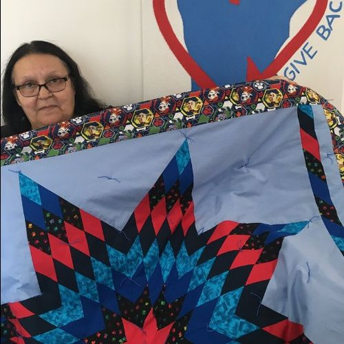 Star quilt maker and Anishinaabe Arts Initiative grantee Flora Jones (Red Lake Nation) displays one of her designs at the Region 2 Arts Council office.