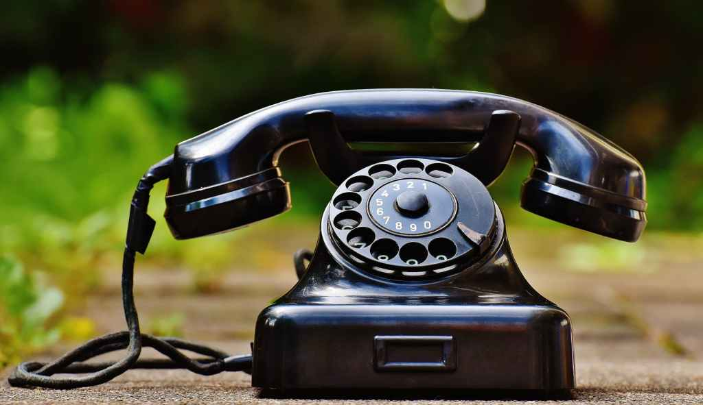 selective focus photography of black rotary phone