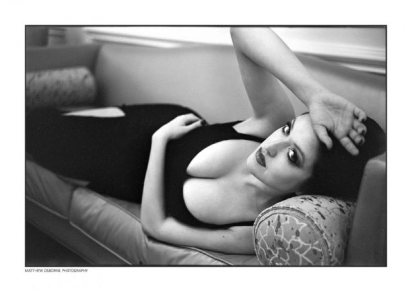 Black and white photo of lady lying down in low cut black dress on Fuji Acros 100 film