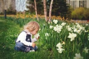 一位小女孩在聞花香