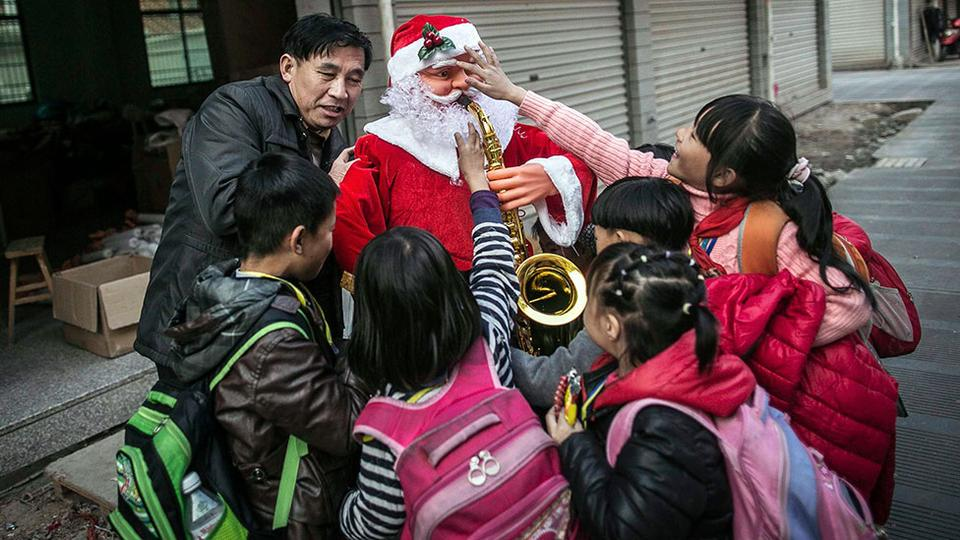 Worker holding a newly made Santa Claus model is surrounded by students in Yiwu
